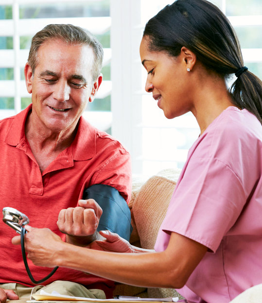female nurse measuring blood pressure of a senior man